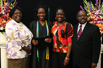 Heald College graduate with family at reception hosted by Warner Pacific at Mt. Scott Church of God May 2015